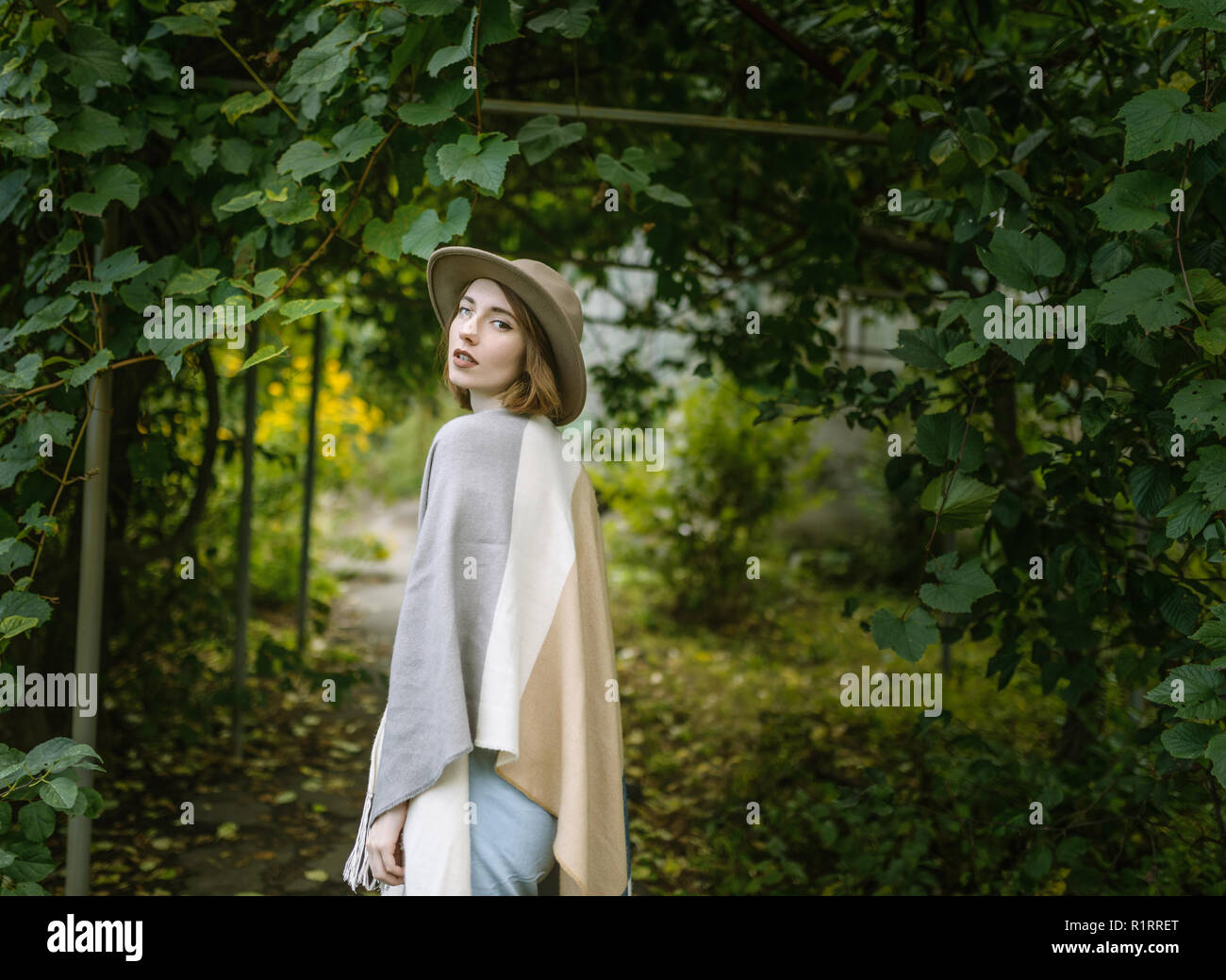 Fashionable young woman wearing in hat and poncho. - Stock Image