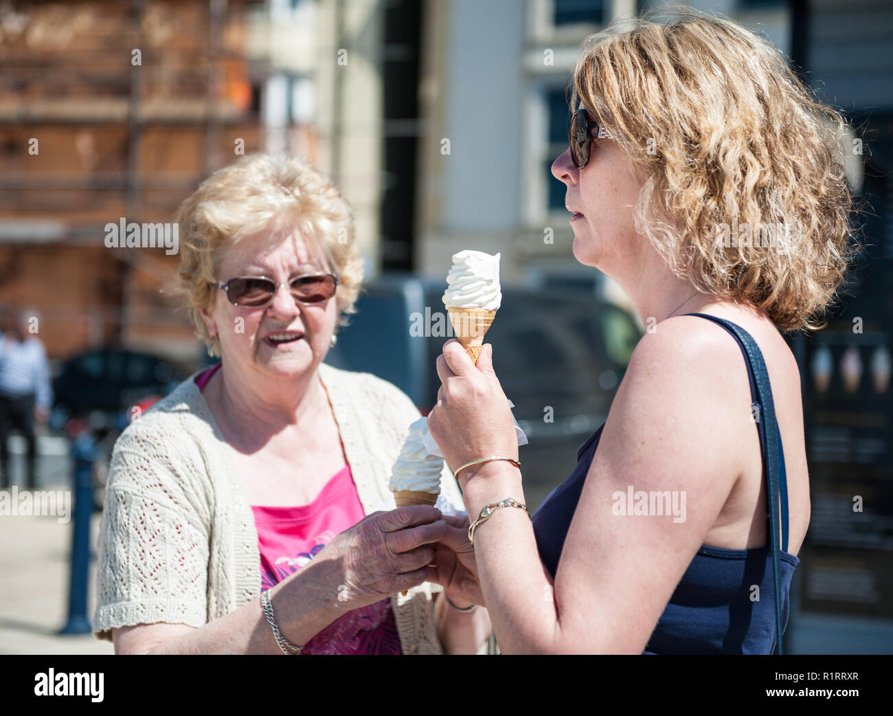 A mother and daughter wnjoy an ice cream on the prom. - Stock Image