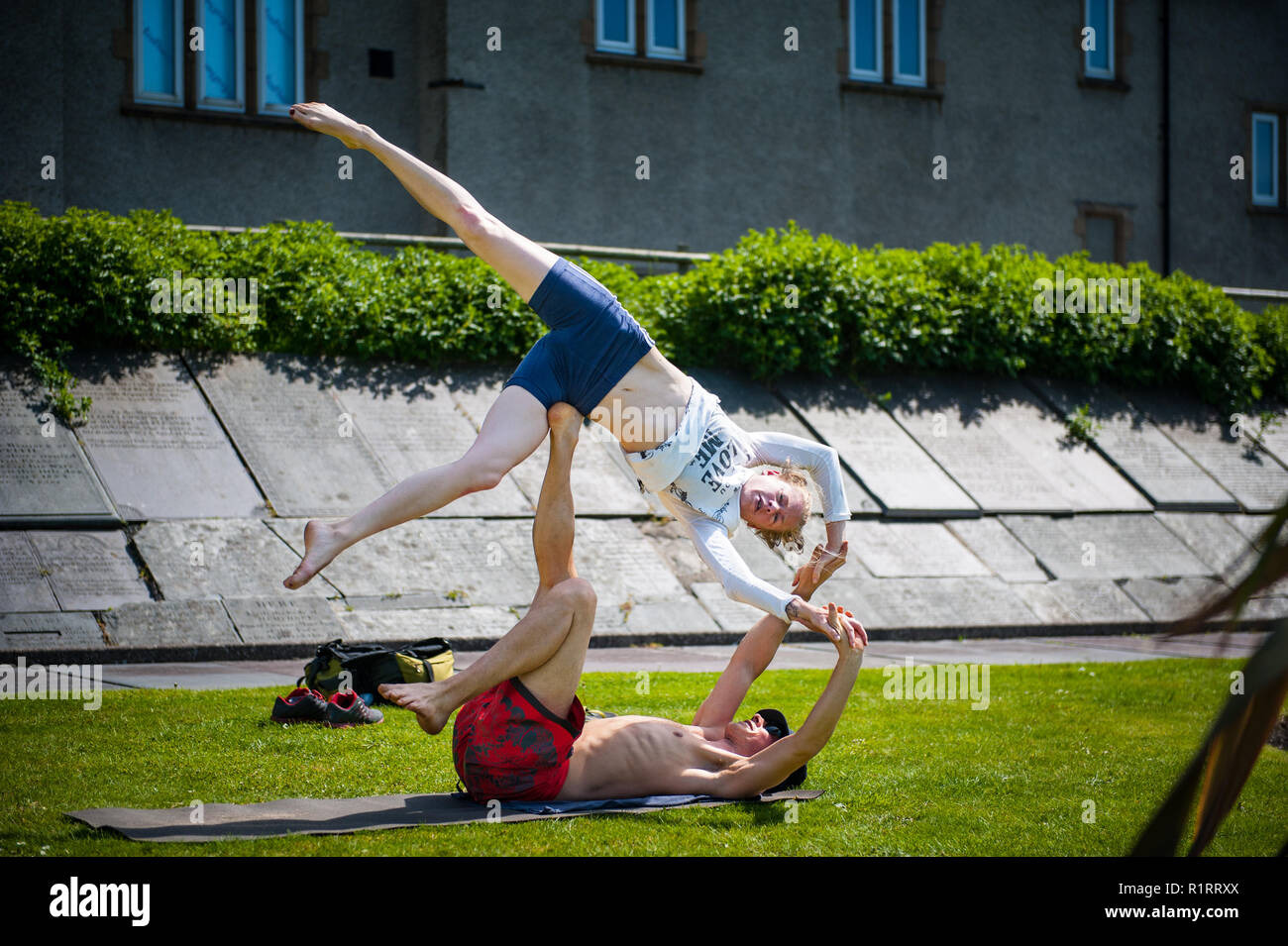 A couple practise 'Yoga Acrobatics' in the old grave yard which is part of the castle grounds. - Stock Image