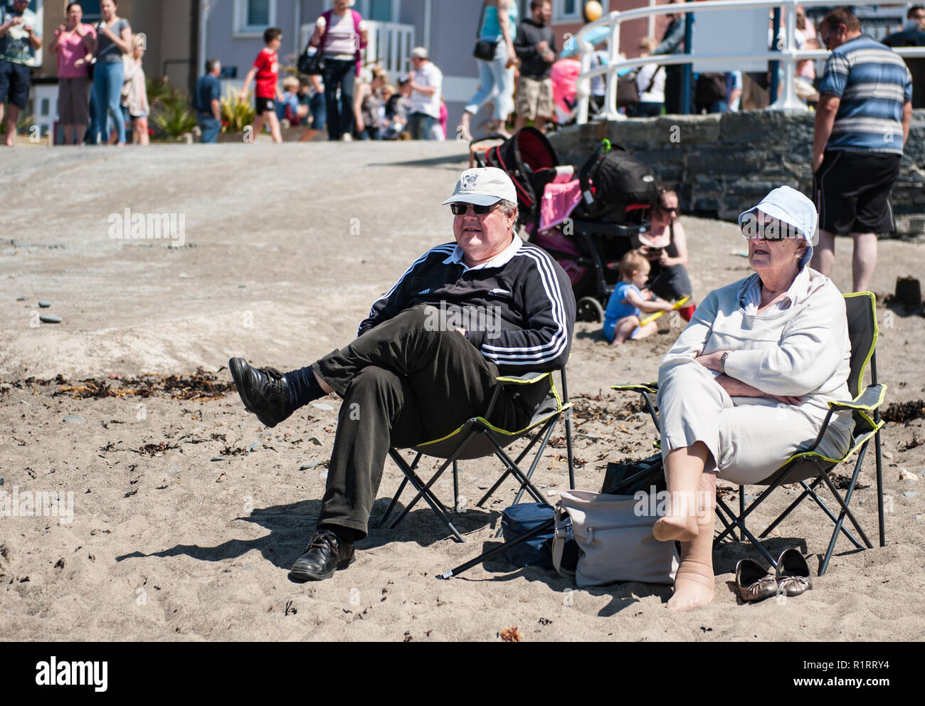An old couple take advantage of the weather and sit relaxing in two chairs in the beach. - Stock Image