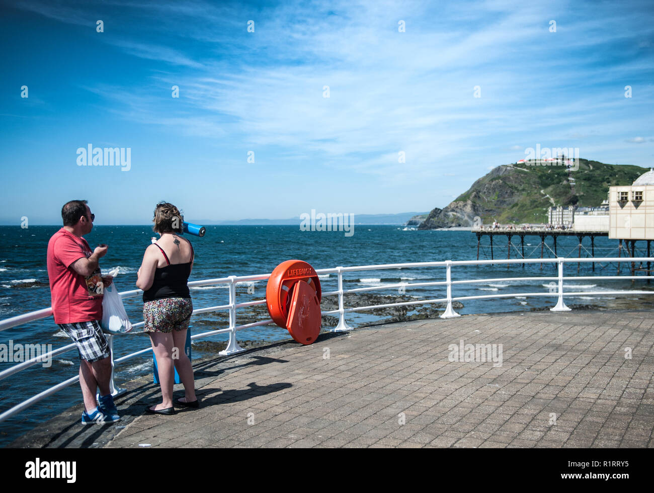 A couple, man and woman enjoy an ice cream whilst taking in the view of the bay. - Stock Image