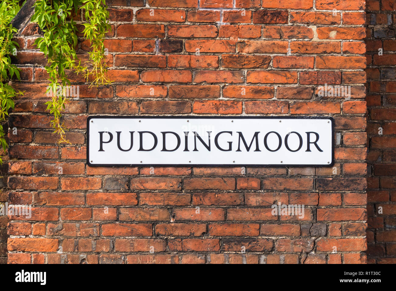 Puddingmoor an unusual road sign road name on a medieval brick wall  Beccles Suffolk England UK Europe - Stock Image