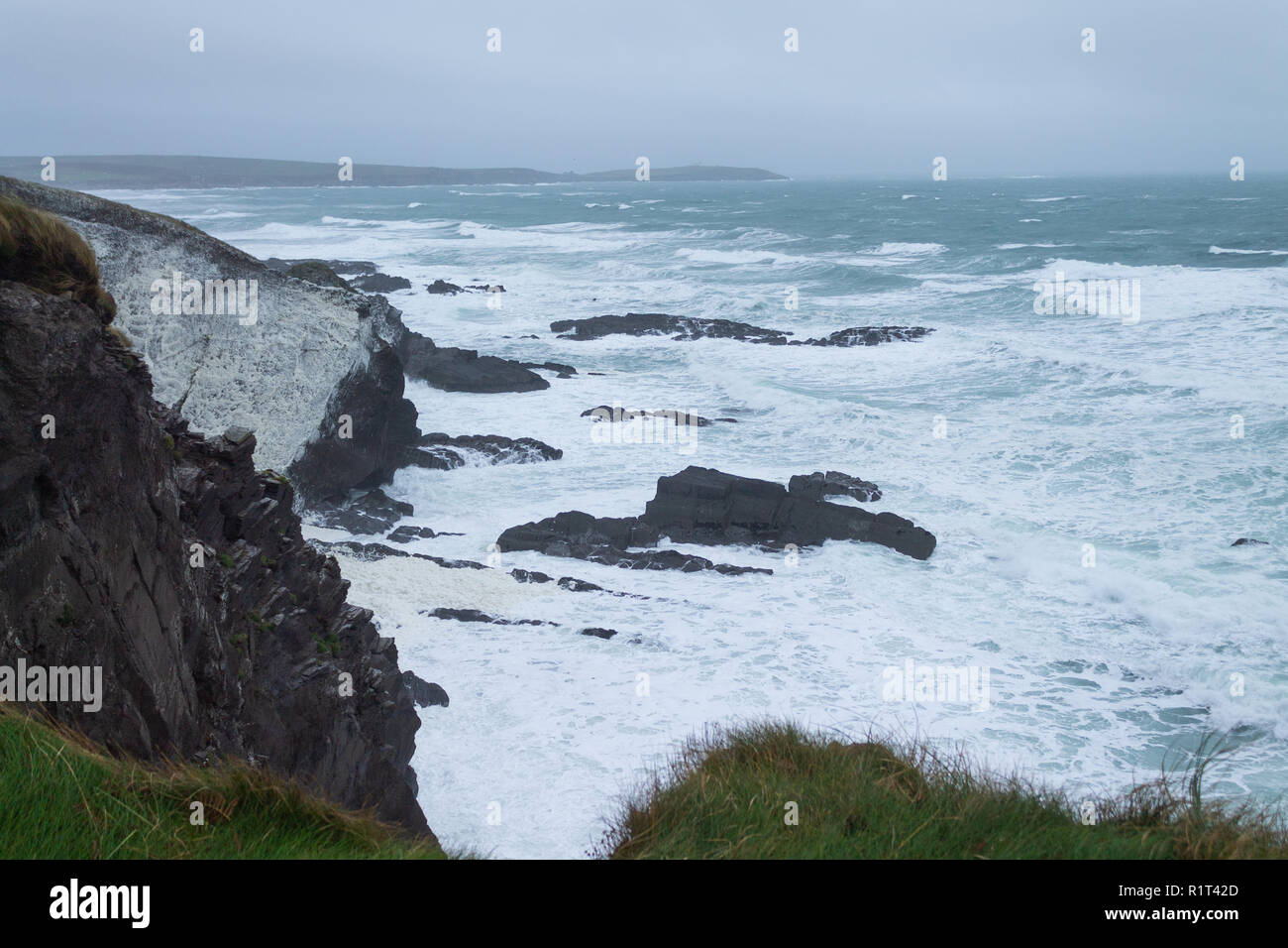 rough sea's covering cliff face in sea foam from a storm. west cork ireland - Stock Image