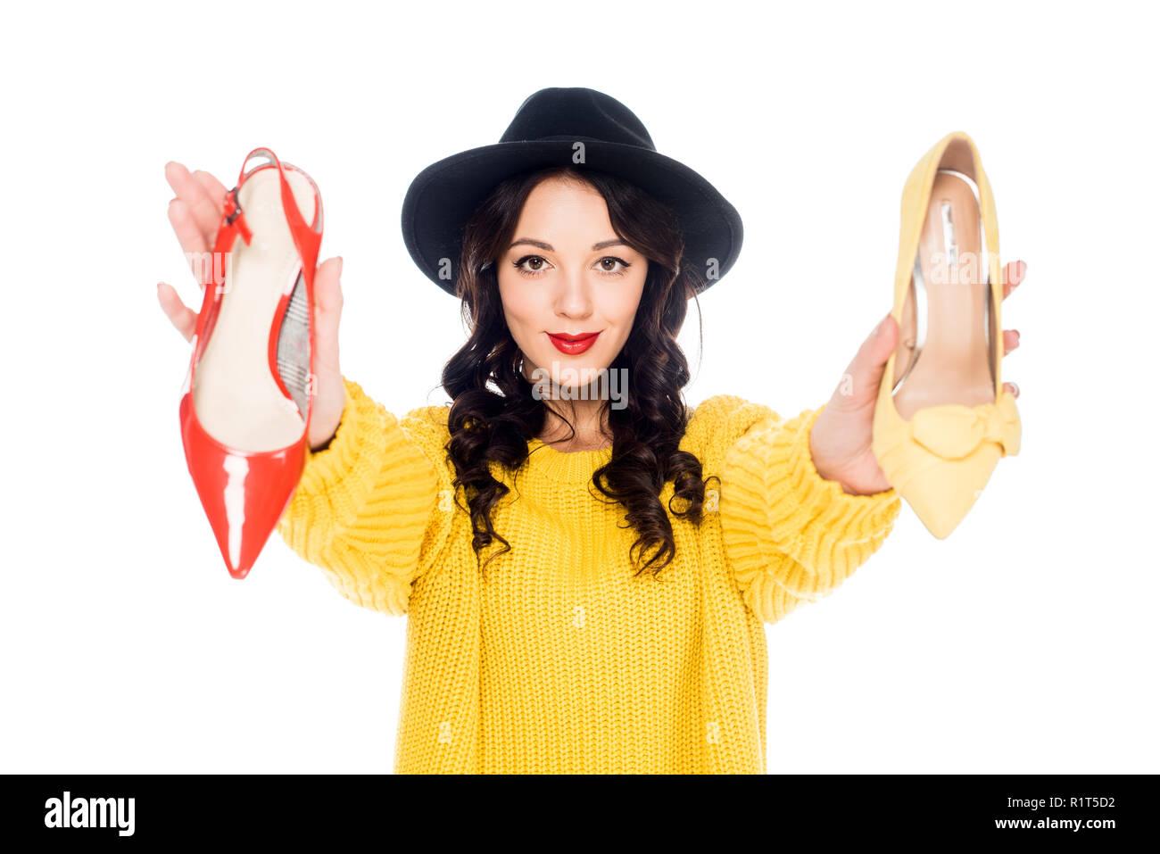 smiling stylish girl holding high heels isolated on white - Stock Image