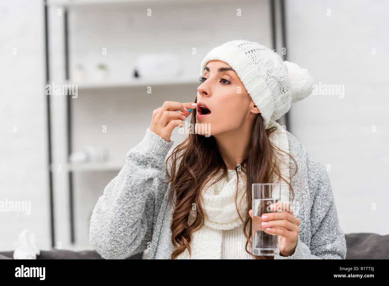 Close Up Portrait Of Sick Young Woman In Warm Clothes Taking Pill At Home