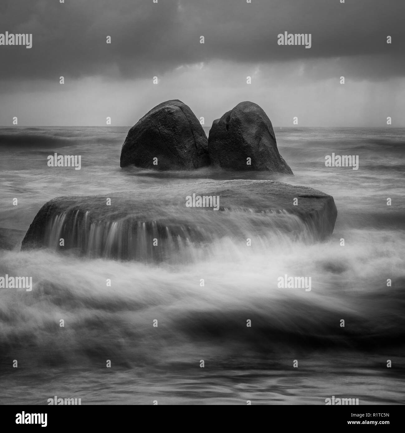 Artistic black and white landscape image of rock being crashed by the waves at the beach with dark cloud before rain. - Stock Image