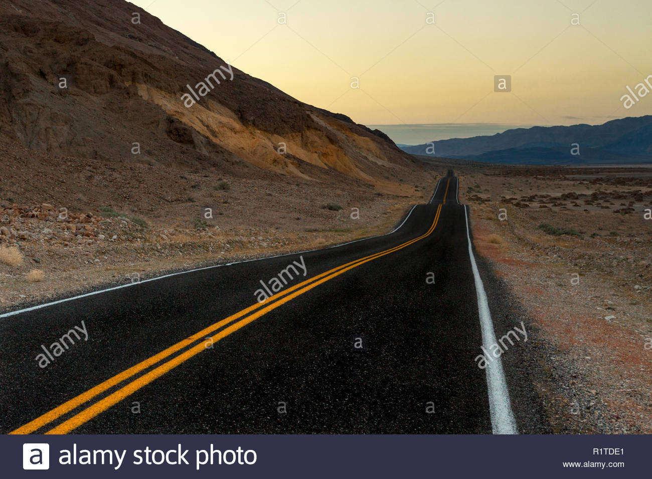 Death Valley National Park sunrise with vanishing point blacktop road - Stock Image