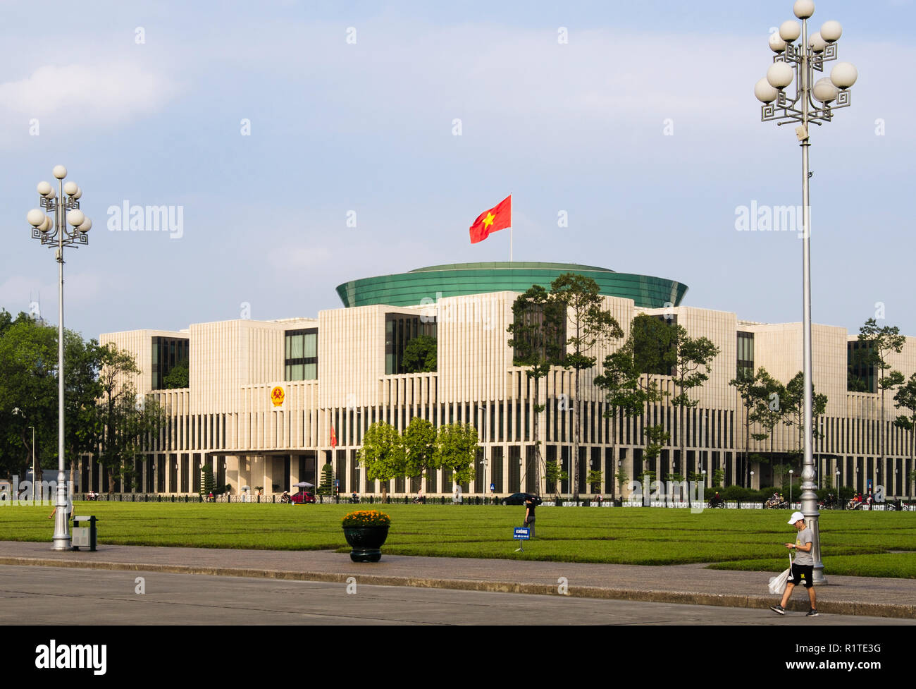 Vietnamese flag flying on new  21st century modern National Assembly House Parliament building. Hanoi, Vietnam, Asia - Stock Image