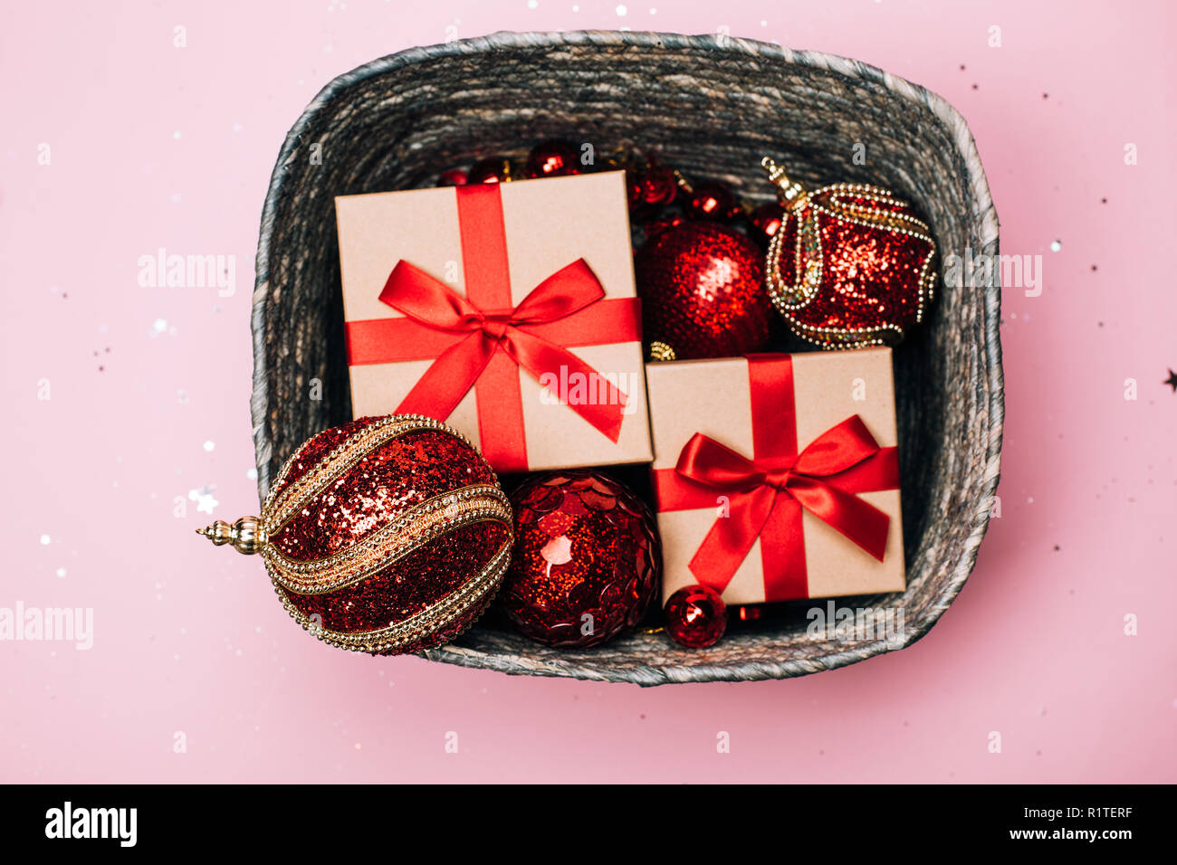 Silver box with presents and red christmas balls on pink pastel background. Flat lay. New year concept. Stock Photo