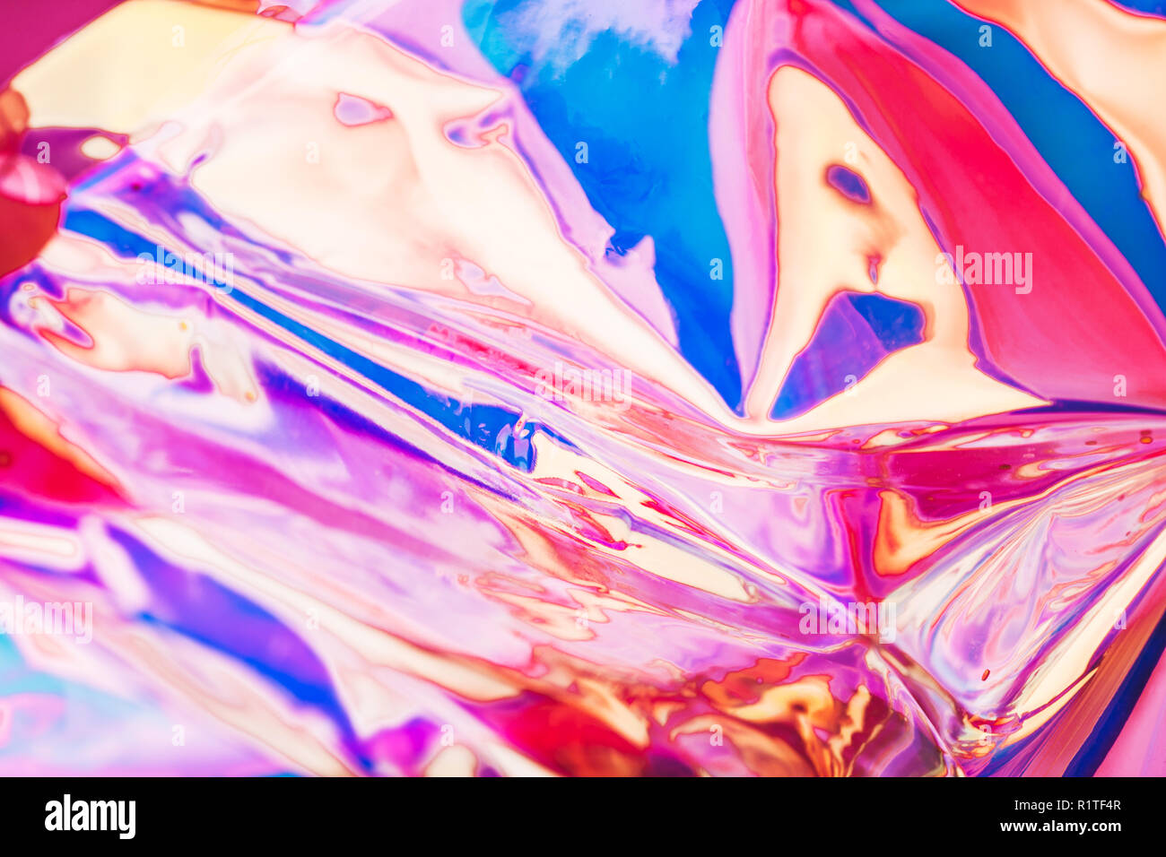Bright holographic foil background. Multicolored and pastel trendy backdrop. - Stock Image