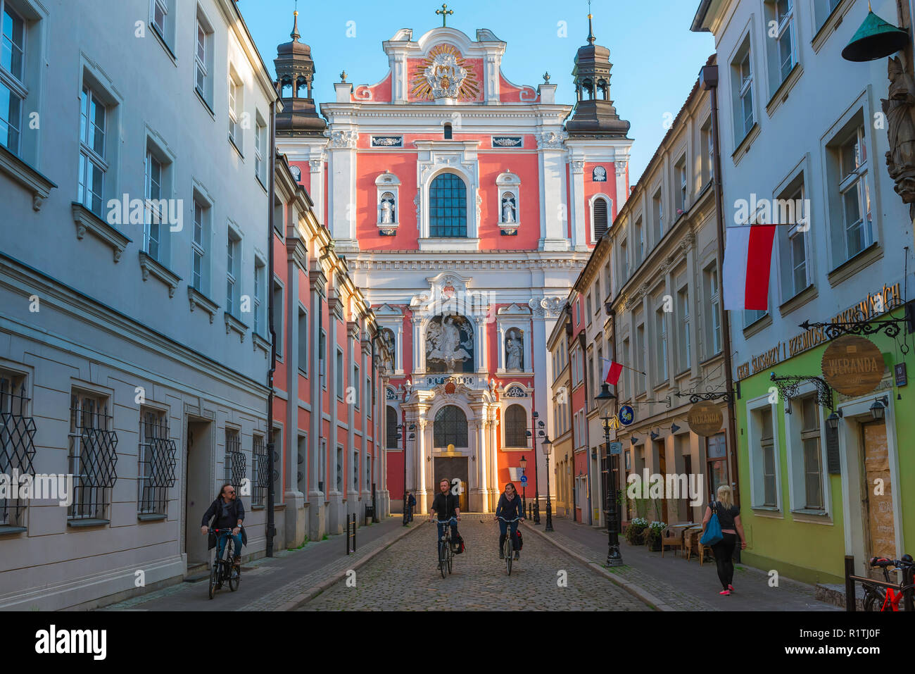 Poznan city Poland, view of people riding their bikes in Poznan Old Town with the Baroque facade of St Stanislaus Church in the background, Poland. - Stock Image