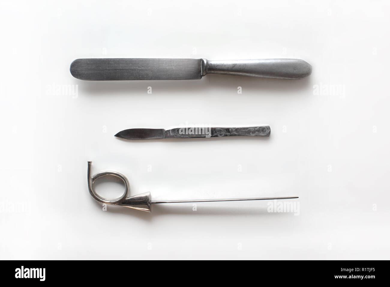Old silver Knife, scalpel and awl isolated on a white background - Stock Image