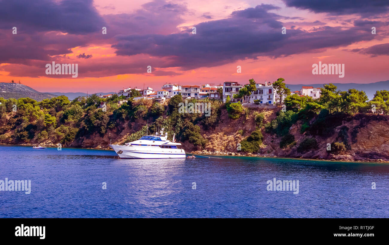 Sunset over Skiathos town, Greece. Luxury yacht in the bay of Skiathos, near the harbour Stock Photo