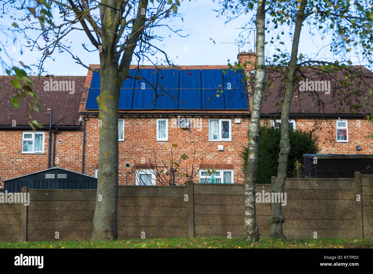 Brick house roof covered with solar panels, uk - Stock Image