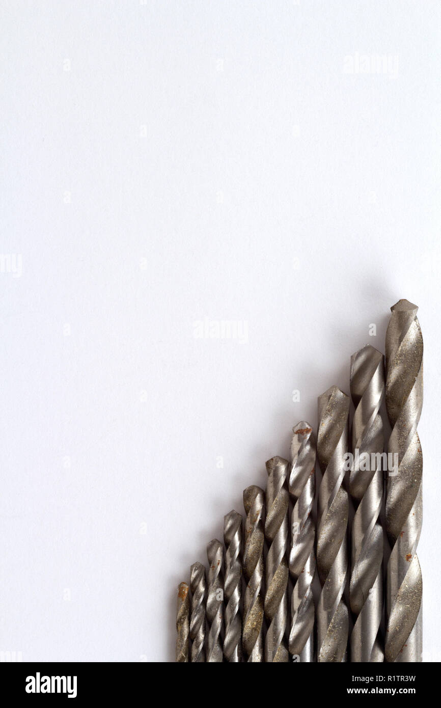 Well used and rust specked twist drill bits on white paper with copy space - Stock Image