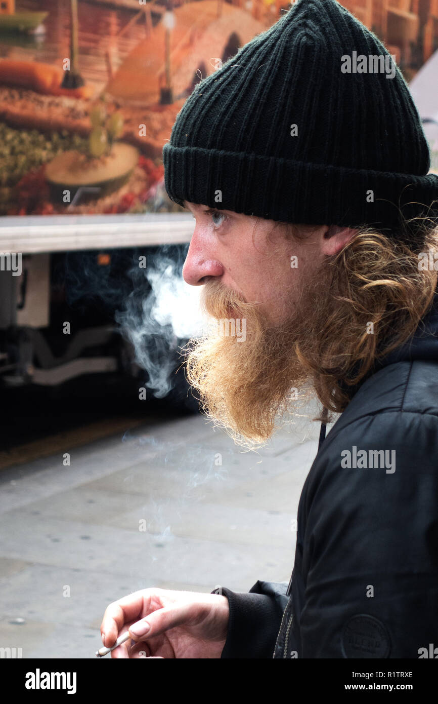 Homeless man standing on the street outside Leicester Square Tube Station - Stock Image