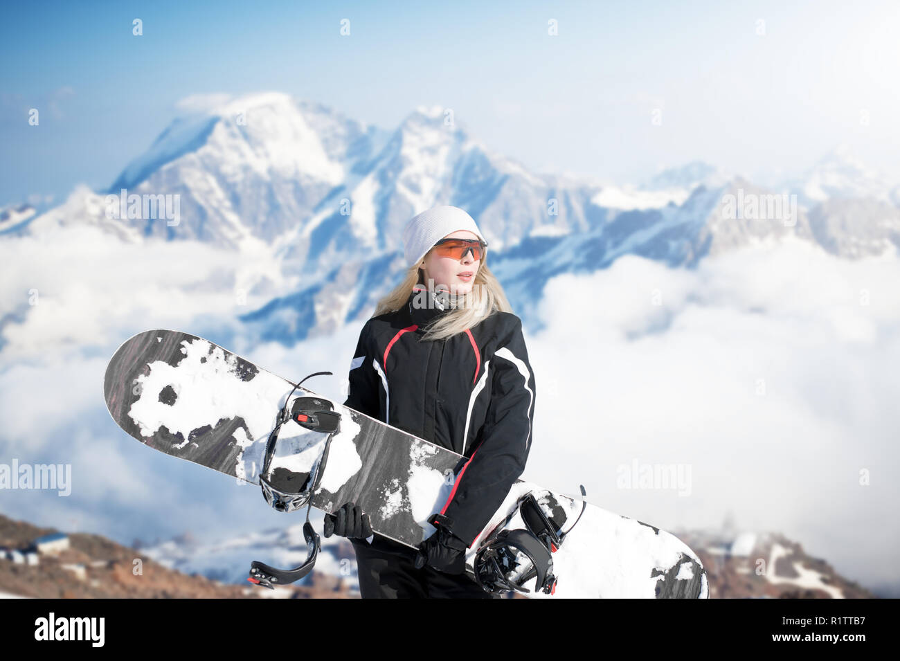 0e57716ab460 Young adult woman snowboarder holding board in hand in snow winter on the  mountainside in fashion