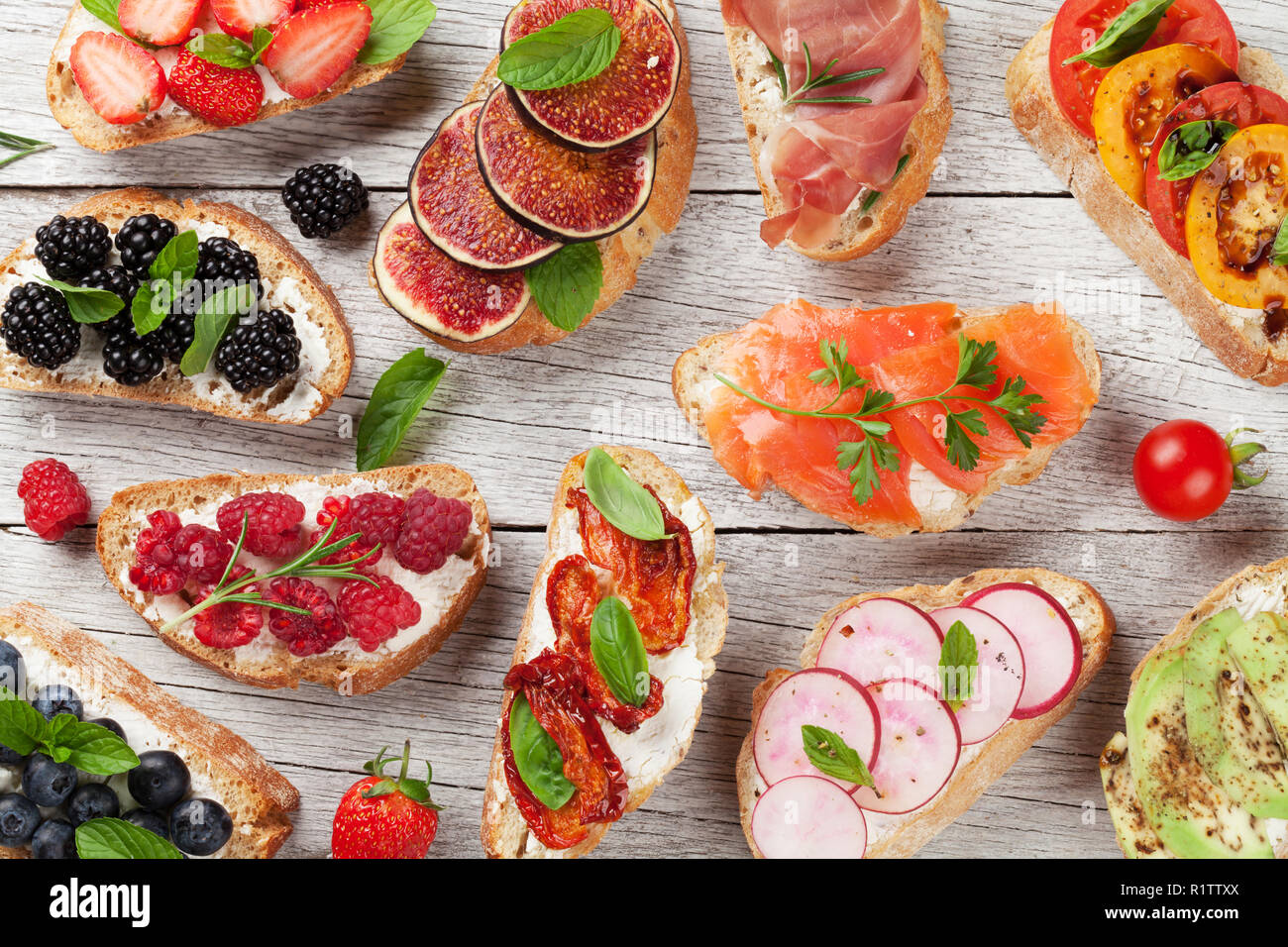 Brushetta or traditional spanish tapas. Appetizers italian antipasti snacks set on wooden board. Top view and flat lay - Stock Image