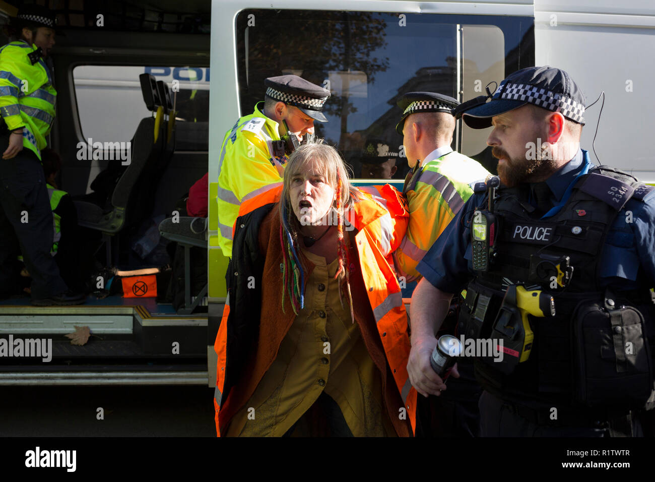 A climate change protester is detained by police officers in Whitehall, on 14th November 2018, in London, England. (Photo by Richard Baker / In Pictures via Getty Images) - Stock Image