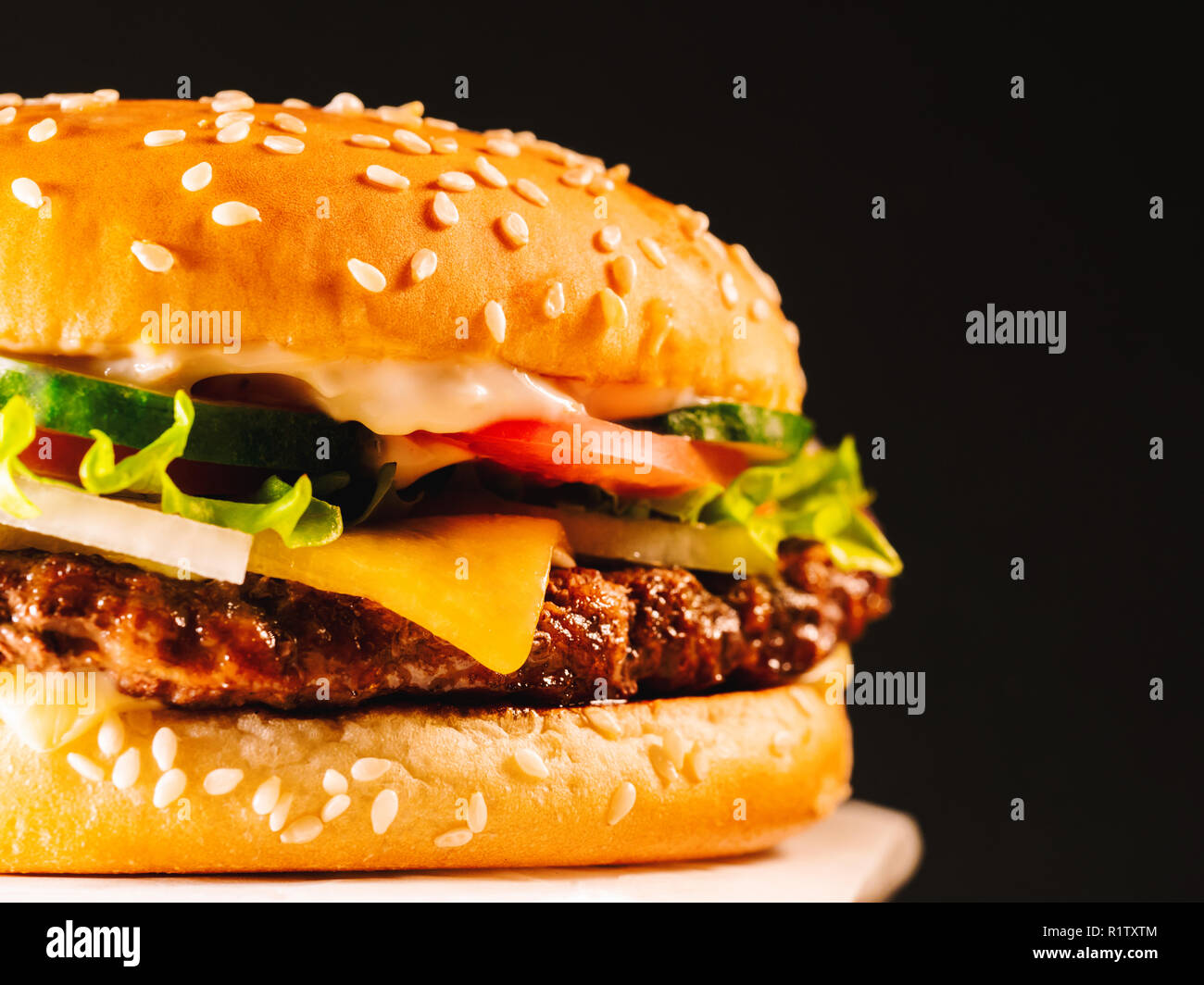 Juicy beef burger with cutlet, onion, vegetables, melted cheese, lettuce, sauce and topped sesame seeds. Isolated hamburger rotates on dark smoke back - Stock Image
