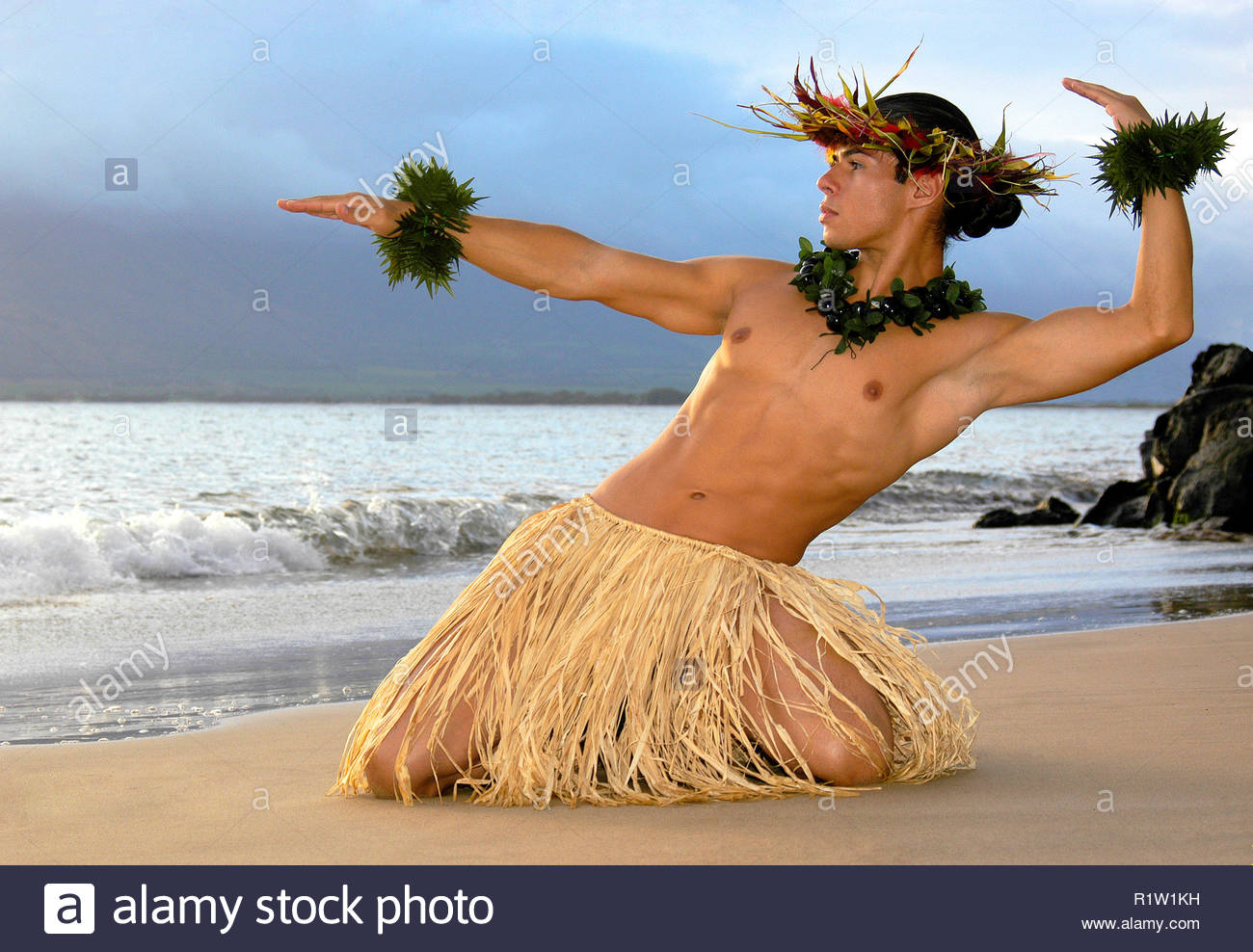 Male hula dancer performs on the beach as the sun sets. Stock Photo