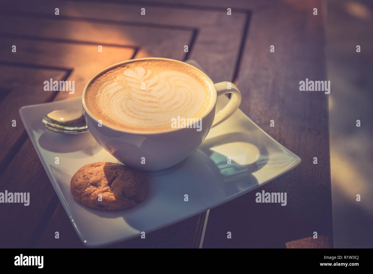 Beautiful morning wooden table top with coffee, latte art and cookie. Start the day, good mood concept. - Stock Image
