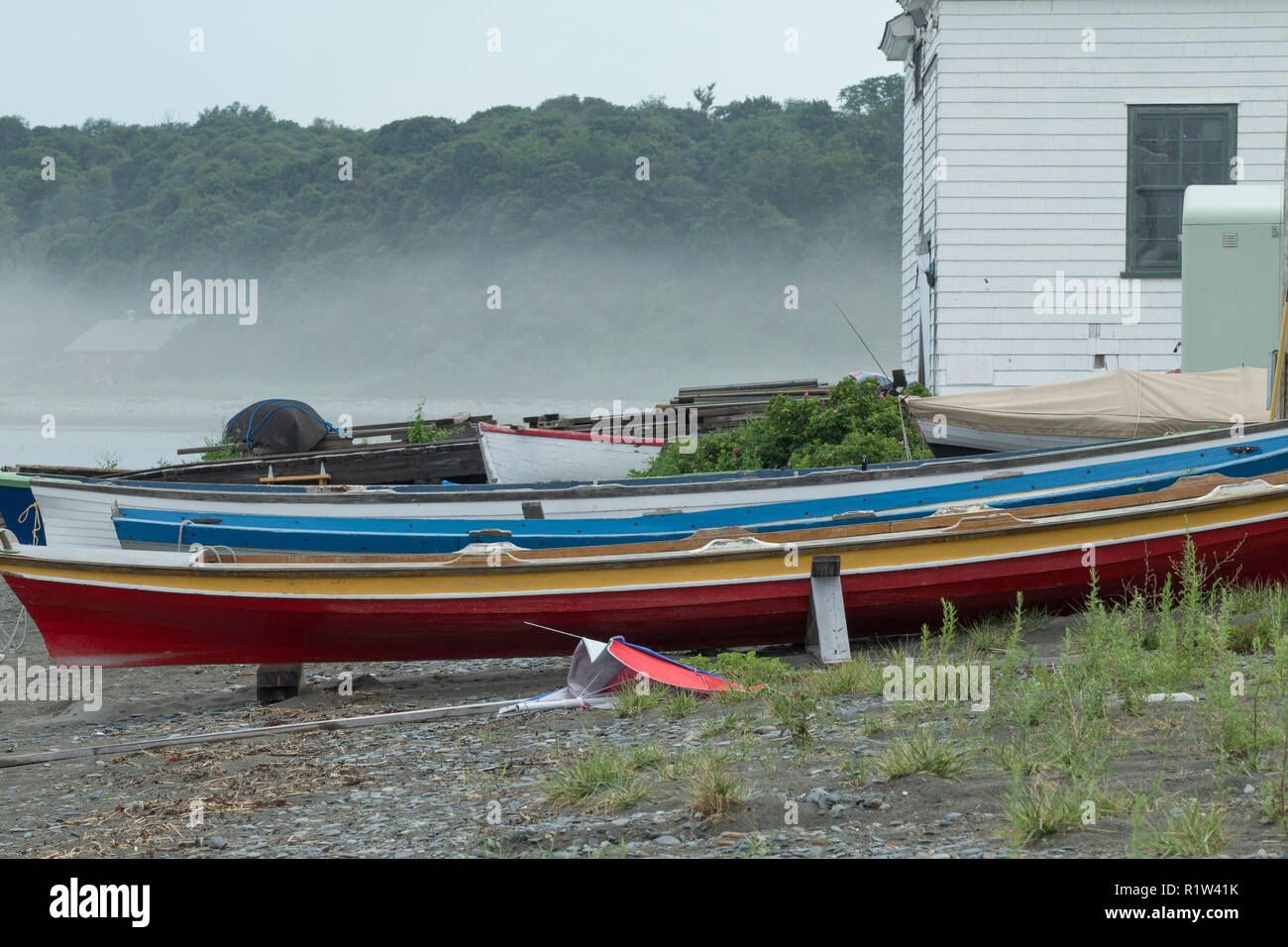 Colorful skiffs along rocky shore in Hull, Mass, a fishing community of blue collar fishermen and their families.Boston Harbor Islands are across cove. - Stock Image