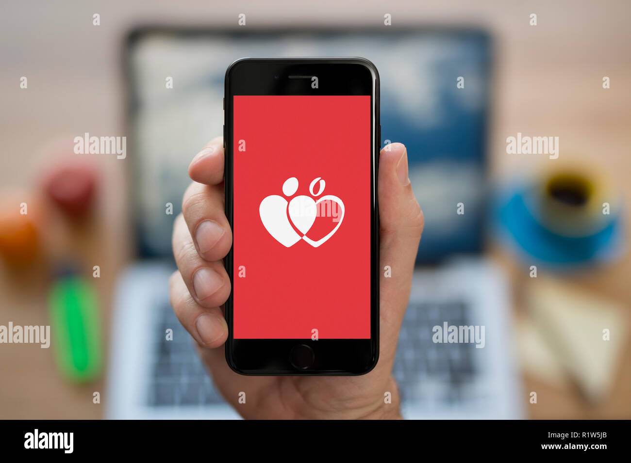 A man looks at his iPhone which displays the Give Blood logo, while sat at his computer desk (Editorial use only). - Stock Image