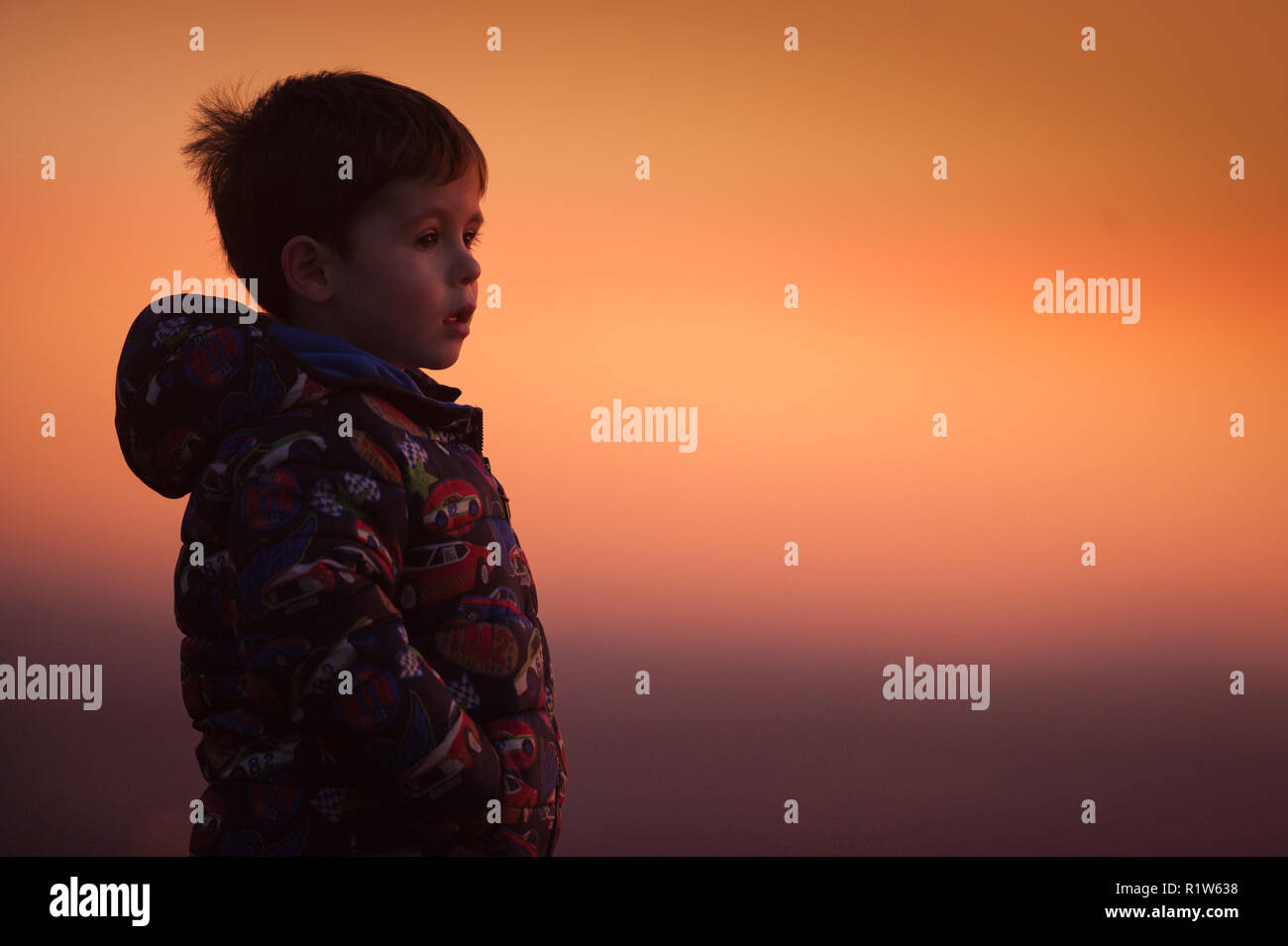 A four year old boy looks out from the top of a hill at sunset taken from the Pennine village of Mossley on Wednesday 14th November 2018. Stock Photo