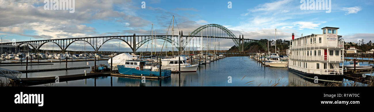 OR02391-00...OREGON - The Newport Bridge spanning Yaquina Bay and boats tied up at a marina below. - Stock Image