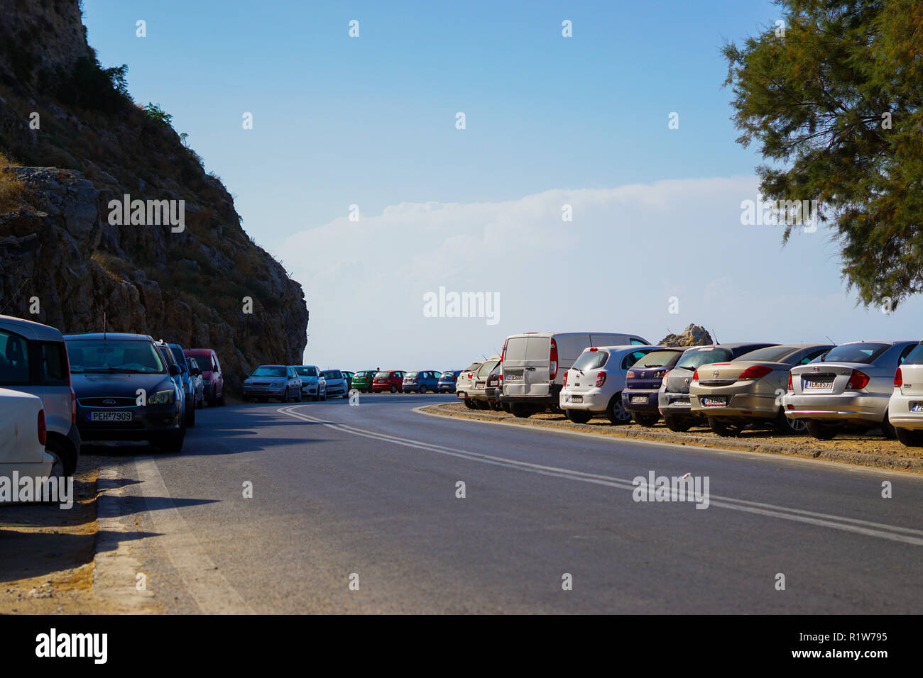 Cars parked along winding road next to cliff. Rethimno, Crete. - Stock Image