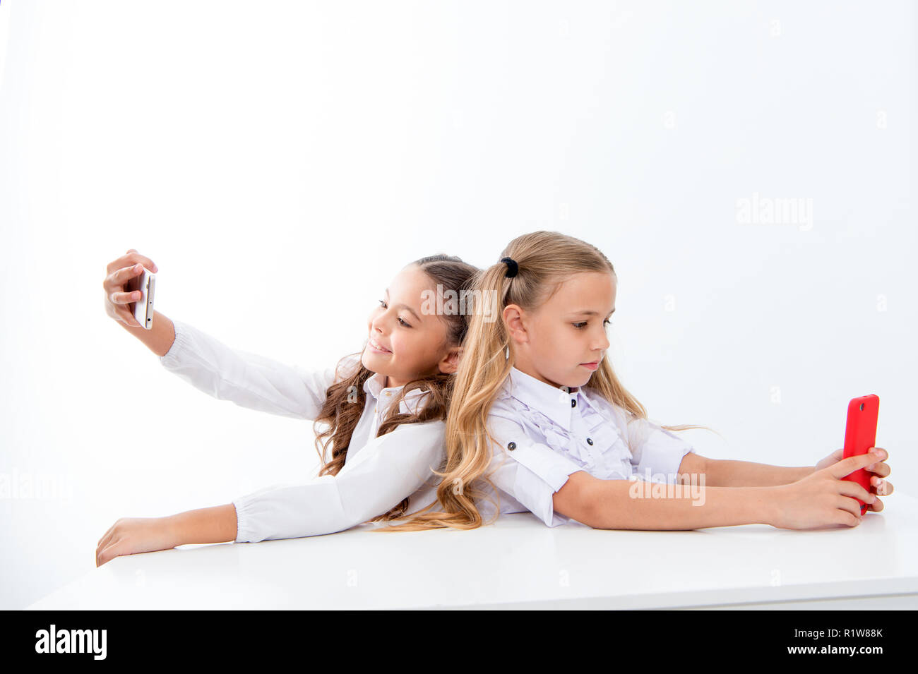 mobile phone dependence and selfie. small kids make selfie on phone at school isolated on white, copy space. students life with mobile phone dependence. - Stock Image