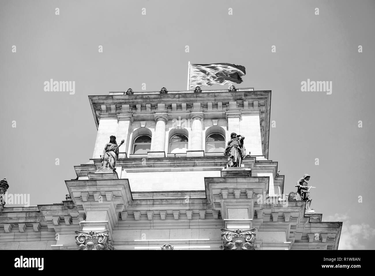 european union flag waving in the wind at famous Reichstag building berlin , seat of the German Parliament Deutscher Bundestag , on a sunny day with blue , central Berlin Mitte district, Germany - Stock Image