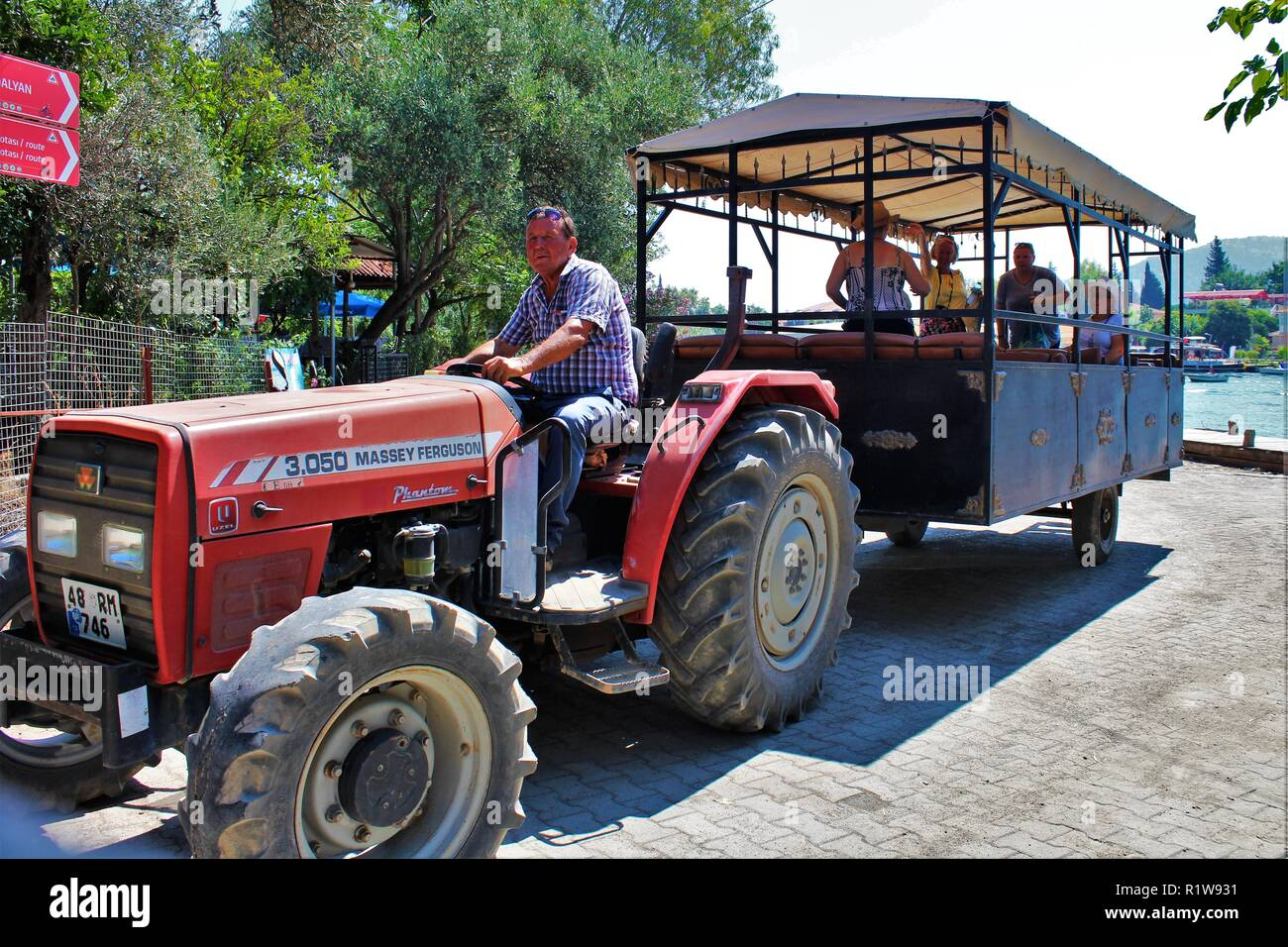 Dalyan, Turkey - July 9th 2018: Tourists embark the tractor shuttle from Dalyan town up to the ancient ruins of Kaunos heritage site. - Stock Image