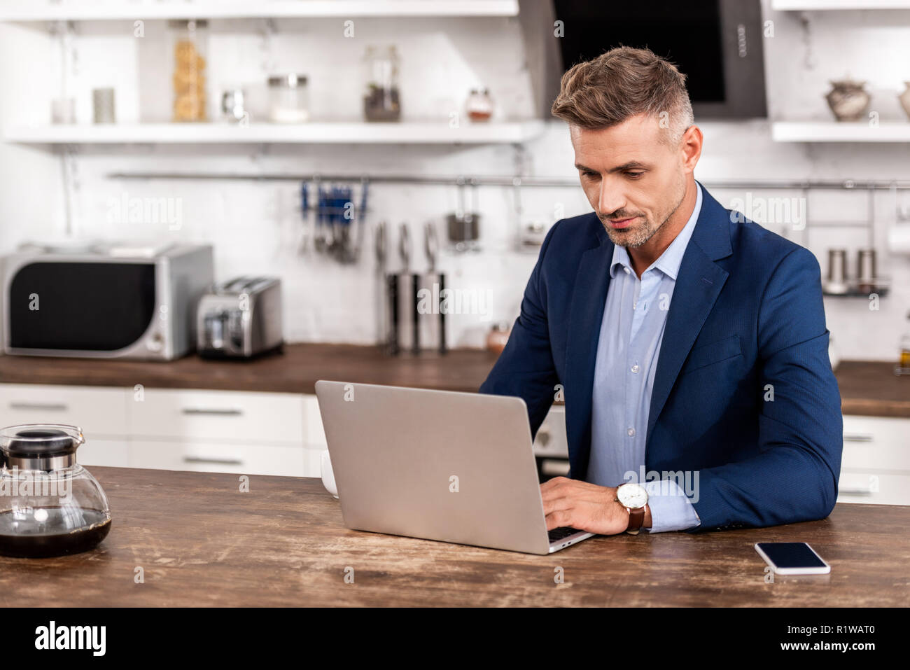 handsome businessman in formal wear using laptop at home - Stock Image