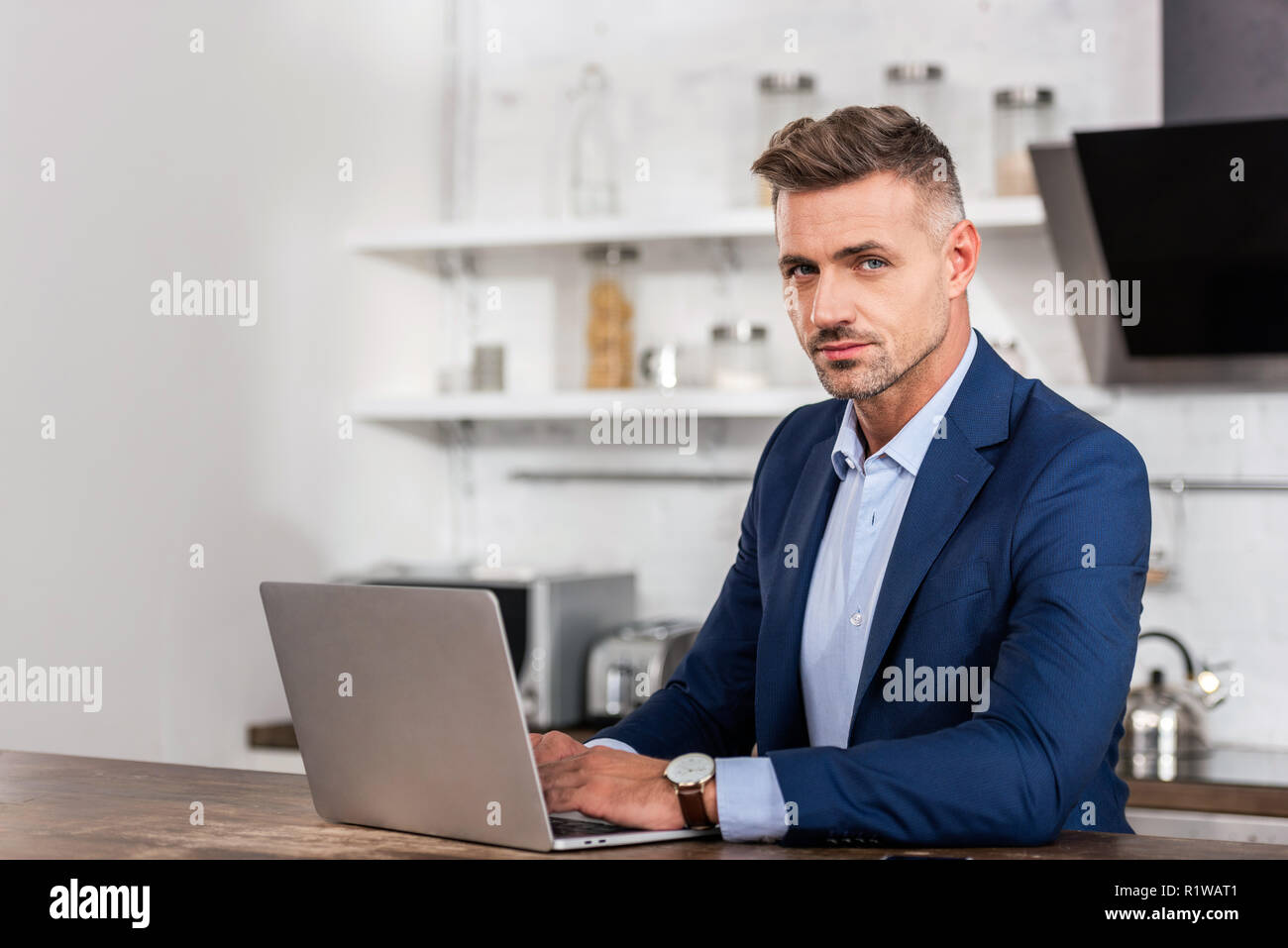 handsome businessman in formal wear looking at camera and using laptop at home - Stock Image