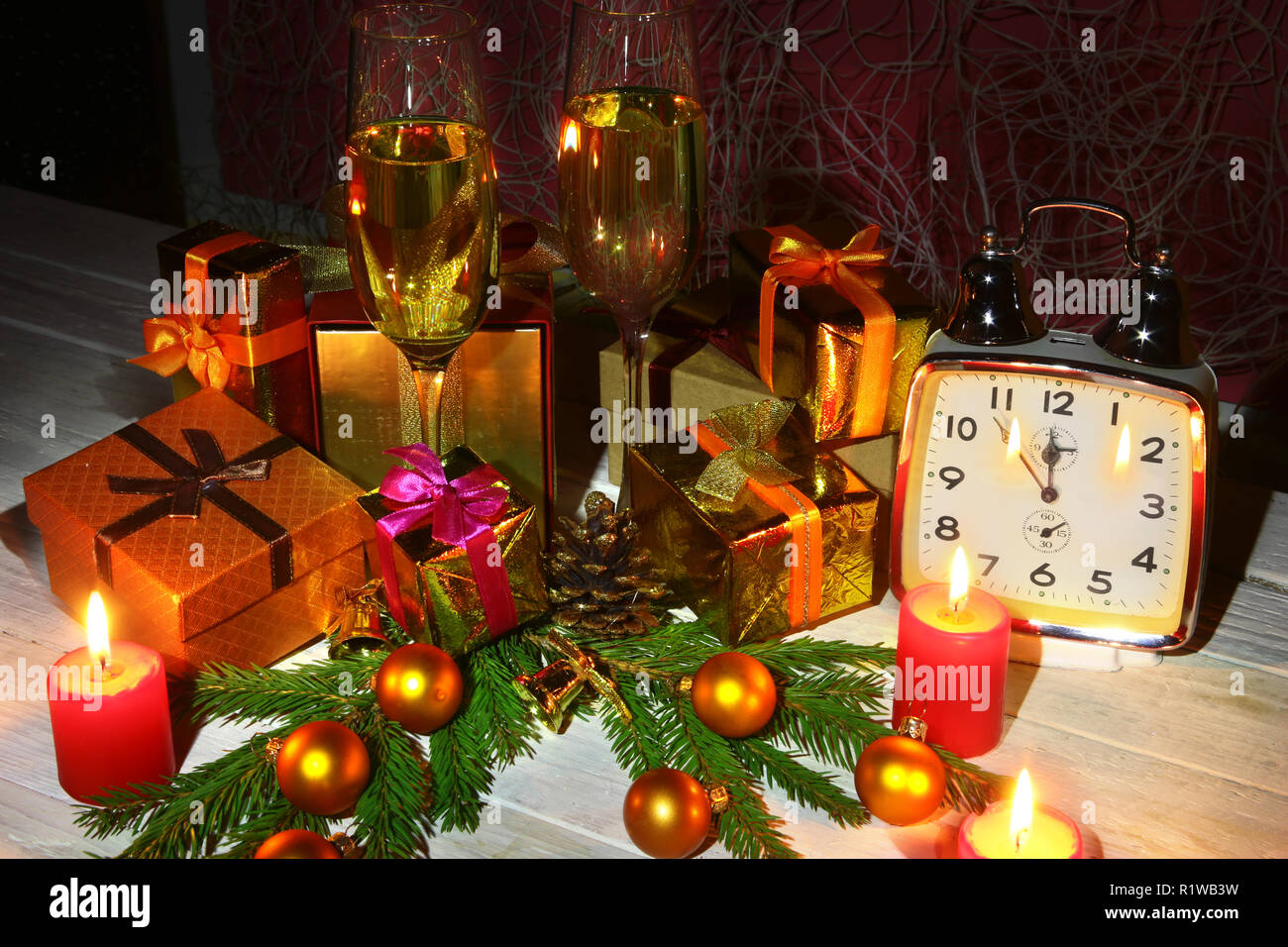new year or christmas decorations with glasses wine gift boxes candles and balls