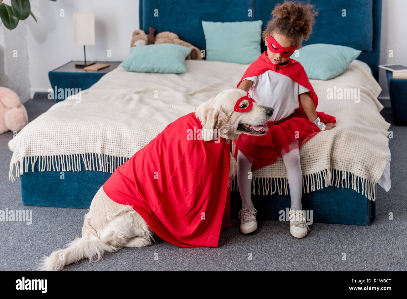 Adorable little african american kid playing with dog in superhero costumes in bedroom - Stock Image