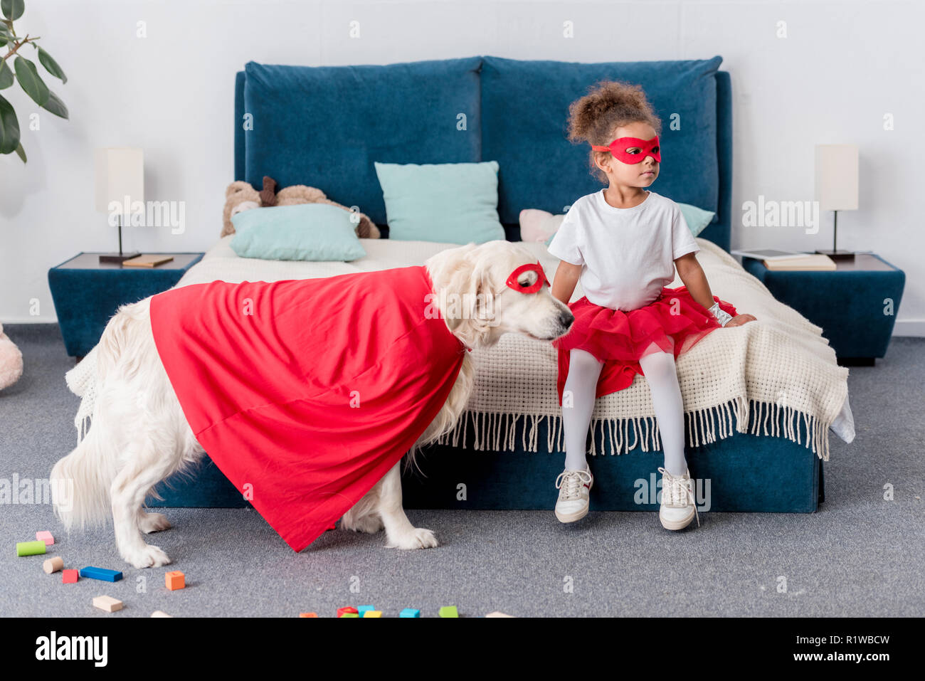Cute little african american kid with dog in superhero costumes in bedroom - Stock Image