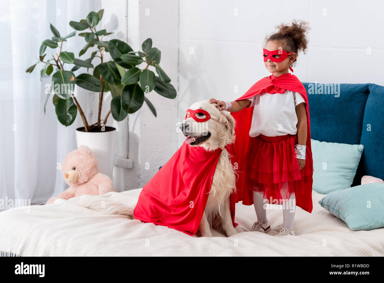 Cute little african american kid with dog in superhero costumes looking away while standing on the bed - Stock Image