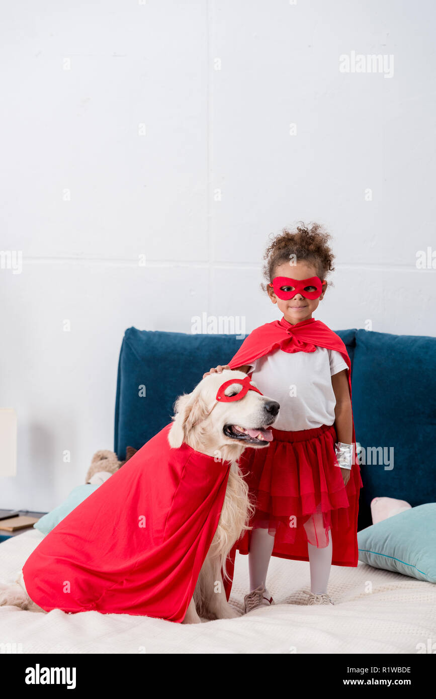 Cute little african american kid with happy dog in red superhero costumes standing on the bed - Stock Image