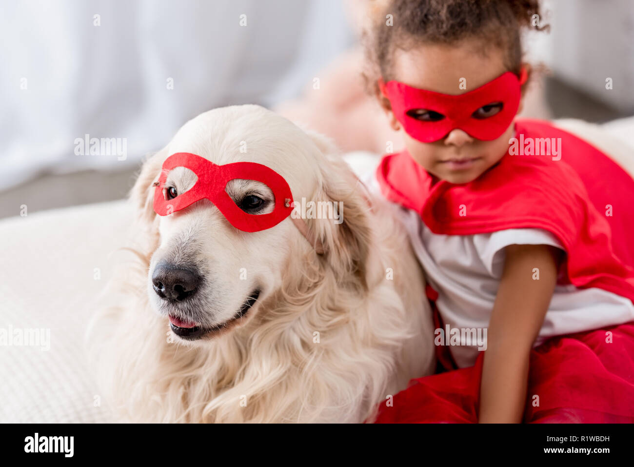 Adorable little african american kid with dog in superhero costumes and red masks - Stock Image