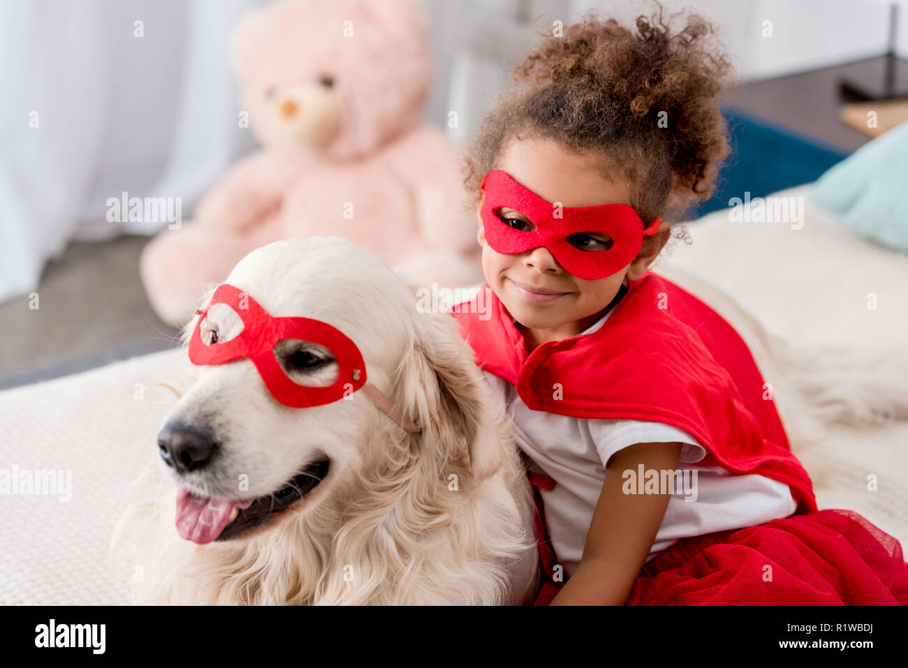Smiling adorable little african american kid with happy dog in red superhero mask - Stock Image