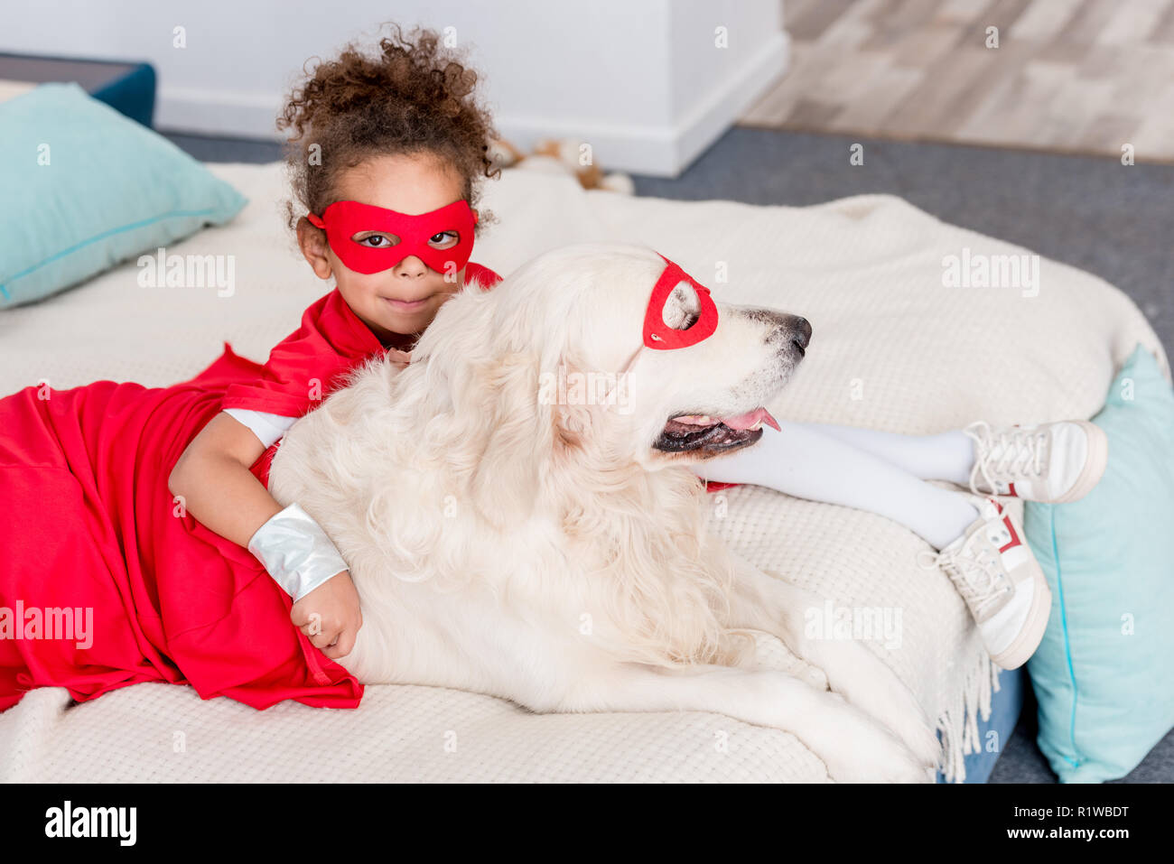 Cute little african american kid with dog in red superhero costumes lying on bed Stock Photo