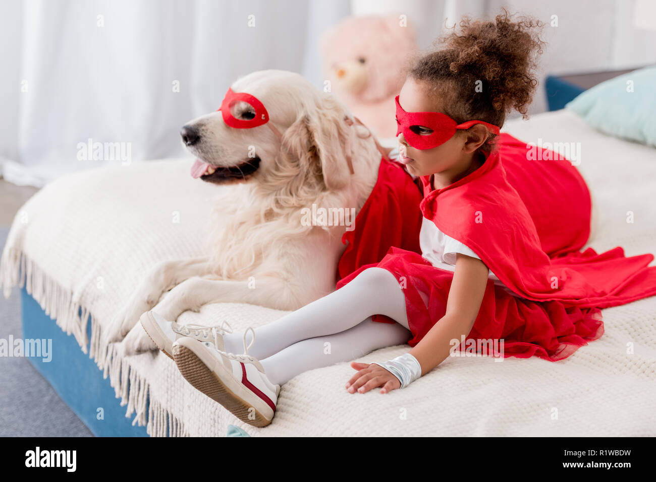 Adorable little african american kid with dog in red superhero costumes sitting on bed - Stock Image