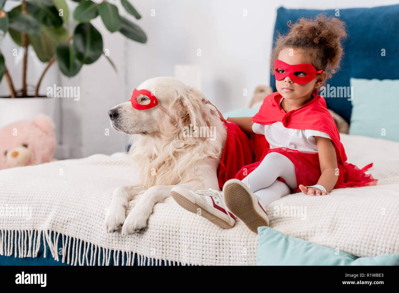 Adorable little african american kid with dog in superhero costumes sitting on bed - Stock Image