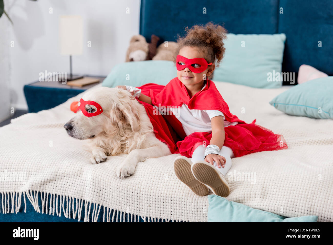 Cute little african american kid with dog in red superhero costumes sitting on bed - Stock Image