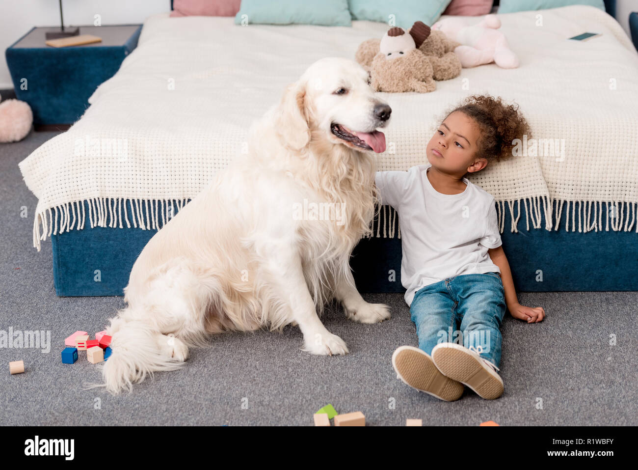 Adorable little african american child sitting on floor with happy dog - Stock Image