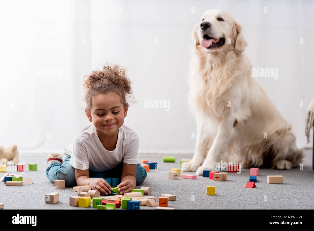 Adorable african american child playing with toy cubes and dog - Stock Image