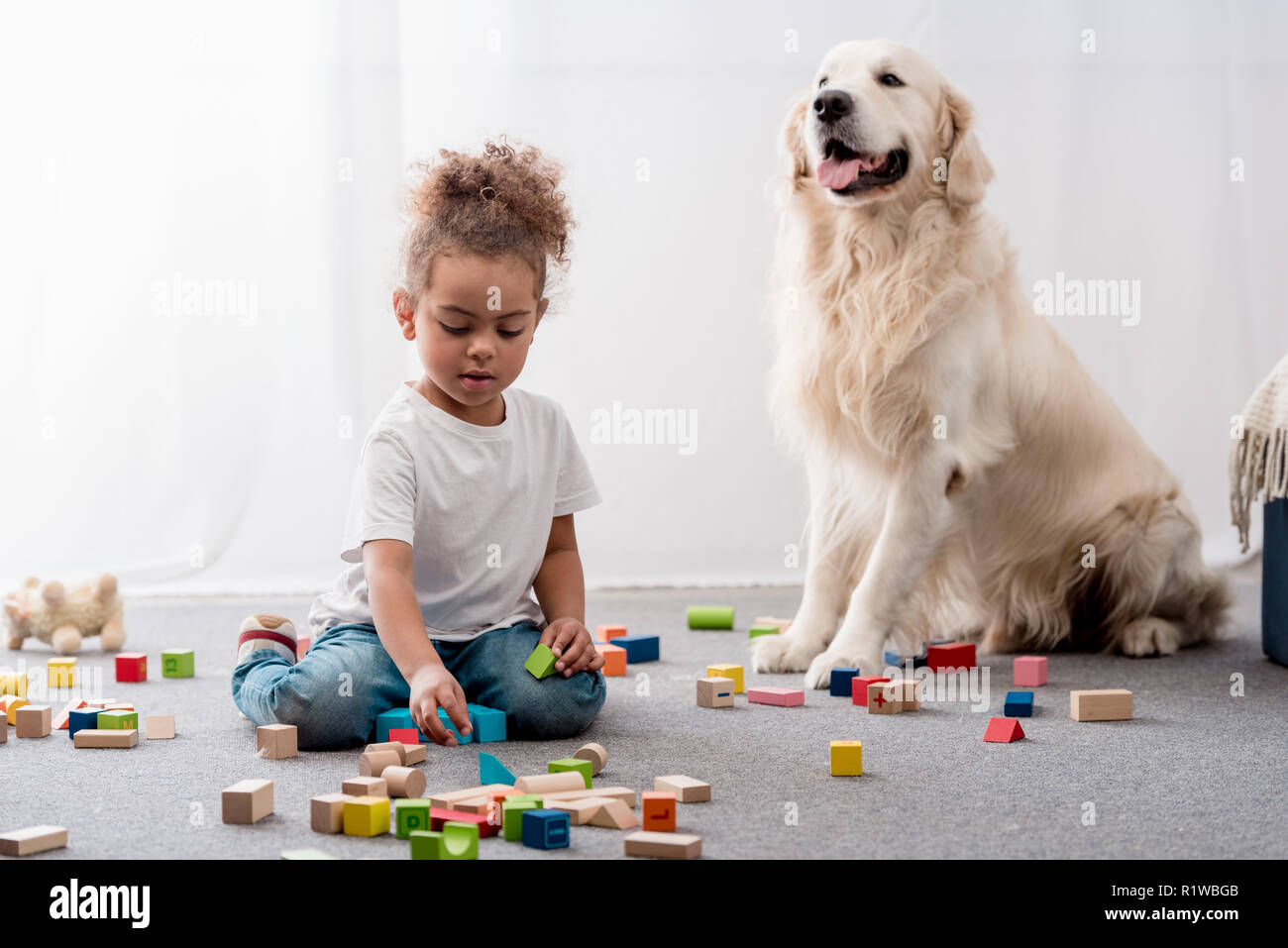 Cute african american child playing with colourful toy cubes and happy dog Stock Photo